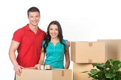 Jeunes couples sur les boîtes en carton de transport de jour mobile Photos stock