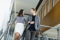 Jeunes couples sur les escaliers dans le bureau photos stock