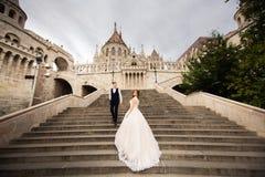 Jeunes couples sur les escaliers sur le fond de l'architecture du pêcheur de bastille photos stock