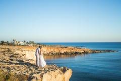 Jeunes couples sur les vacances d'été de plage, l'homme de sourire heureux et le voyage de marche de vacances d'océan de mer de b Photos libres de droits