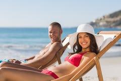 Jeunes couples sur leurs chaises de plate-forme souriant à l'appareil-photo Photographie stock libre de droits