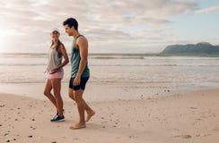 Jeunes couples sur marcher le long du rivage Images stock