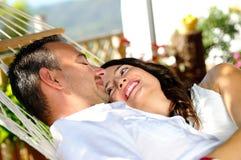Jeunes couples sur un hamac de corde dans une vue de partie latérale de cottage Images stock
