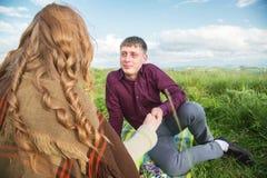 Jeunes couples sur un pique-nique dans un bel endroit sous le ciel ouvert Photographie stock