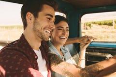 Jeunes couples sur un voyage par la route conduisant dans la voiture Images libres de droits