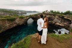 Jeunes couples sur une falaise devant l'océan photos libres de droits