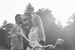 Jeunes couples sur une moto dans le domaine Image stock