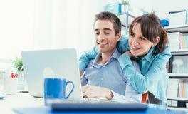 Jeunes couples surfant le Web à la maison Photo stock