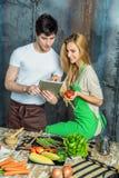 Jeunes couples surfant le Web dans la cuisine Image stock