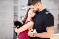 Jeunes couples tenant des chats dans des mains sur la terrasse Image libre de droits