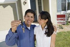 Jeunes couples tenant des clés en dehors de nouveau portrait à la maison photo stock