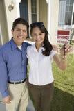 Jeunes couples tenant des clés en dehors de nouveau portrait à la maison image stock