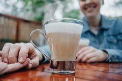 Jeunes couples tenant des mains au café de rue, plan rapproché image stock