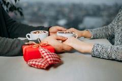 Jeunes couples tenant des mains ayant la date au café au jour de valentines Image stock