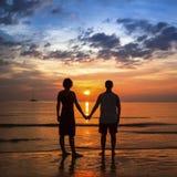 Jeunes couples tenant des mains sur la côte d'océan pendant le coucher du soleil étonnant Image stock