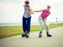 Jeunes couples tenant des mains tout en faisant du roller Images stock