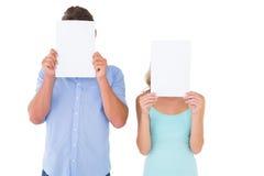 Jeunes couples tenant des pages au-dessus de leurs visages Photos libres de droits