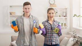 Jeunes couples tenant l'équipement de nettoyage à la maison Photo libre de droits