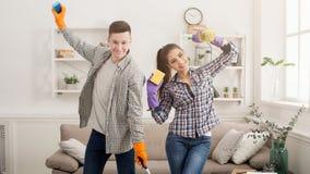 Jeunes couples tenant l'équipement de nettoyage à la maison Photographie stock libre de droits