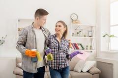 Jeunes couples tenant l'équipement de nettoyage à la maison Photos stock