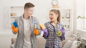 Jeunes couples tenant l'équipement de nettoyage à la maison Images stock