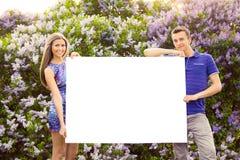 Jeunes couples tenant l'affiche vide Image stock
