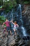 Jeunes couples tenant la cascade proche avec leurs vélos Photographie stock libre de droits