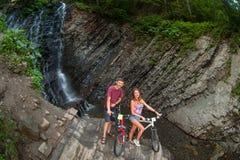Jeunes couples tenant la cascade proche avec leurs vélos Image stock