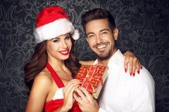 Jeunes couples tenant le cadeau à Noël Images stock