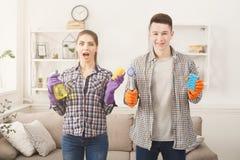 Jeunes couples tenant le fond intérieur d'équipement de nettoyage à la maison Image libre de droits