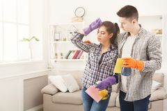 Jeunes couples tenant le fond intérieur d'équipement de nettoyage à la maison Photographie stock