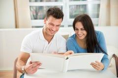 Jeunes couples tenant le modèle de maison verte Images libres de droits