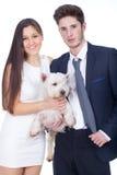 Jeunes couples tenant un chien blanc Photos stock