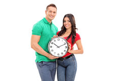 Jeunes couples tenant une grande horloge murale Images stock