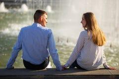 Jeunes couples timides se reposant près de la fontaine tenant des mains à leur f Photos stock