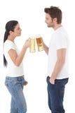 Jeunes couples tintant avec des tasses de sourire de bière Image libre de droits