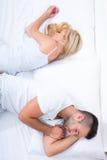 Jeunes couples tournant de nouveau à l'un l'autre dans le lit Image libre de droits