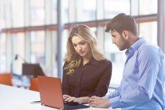 Jeunes couples travaillant ensemble sur un ordinateur portable dans le bureau concepts de travail d'équipe Photo stock