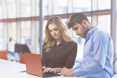 Jeunes couples travaillant ensemble sur un ordinateur portable dans le bureau concepts de travail d'équipe Photographie stock libre de droits