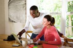 Jeunes couples travaillant ensemble sur un ordinateur portatif photos stock
