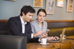 Jeunes couples travaillant sur l'ordinateur portable au café Photo stock