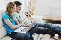 Jeunes couples travaillant sur l'ordinateur portatif à la maison Photographie stock libre de droits