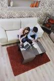 Jeunes couples travaillant sur l'ordinateur portatif à la maison Photographie stock