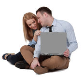 Jeunes couples travaillant sur un ordinateur portatif Image stock