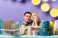 Jeunes couples tristes ayant une coupure tout en faisant quelques travaux du m?nage photos libres de droits