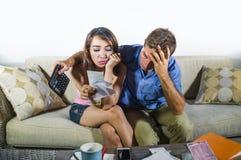 Jeunes couples tristes et inquiétés attrayants rendant compte ensemble dans f Photo libre de droits