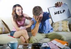Jeunes couples tristes et inquiétés attrayants rendant compte ensemble dans le divan d'effort financier à la maison dans le probl Image libre de droits