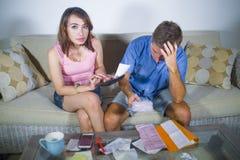 Jeunes couples tristes et inquiétés attrayants rendant compte ensemble dans le divan d'effort financier à la maison dans le probl Photo libre de droits