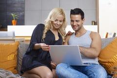 Jeunes couples utilisant l'ordinateur portable à la maison Image stock