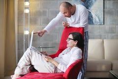 Jeunes couples utilisant l'ordinateur portable à la maison Photographie stock libre de droits